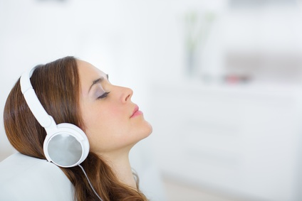 young female with headphones relaxing at home